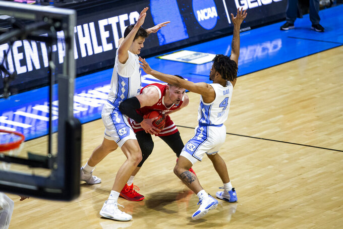 Wisconsin's Micah Potter, center, gets pressure from North Carolina's Walker Kessler, left, and RJ Davis (4) during the first half of a first-round game in the NCAA men's college basketball tournament Friday, March 19, 2021, at Mackey Arena in West Lafayette, Ind. (AP Photo/Robert Franklin)
