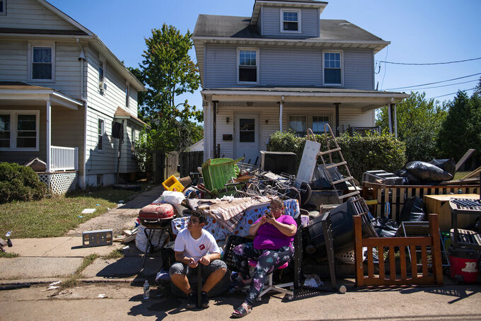 """FILE - Residents wait for President Joe Biden's motorcade to pass by one of the streets affected by Hurricane Ida in Manville, N.J., Tuesday, Sept. 7, 2021. Not even a month after Ida's torrential leftovers dumped nearly a foot of rain in a few hours in places, turning roads into waterways and leaving 30 people dead, New Jersey's top environmental regulator said this week the state's floodplain property buyback program """"definitely needs expansion."""" (AP Photo/Eduardo Munoz Alvarez, File)"""