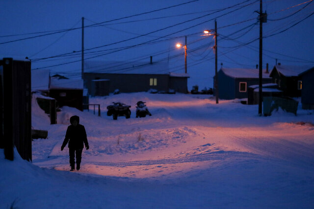 FILE - In this Jan. 20, 2020, file photo, a woman walks before dawn in Toksook Bay, Alaska, a mostly Yup'ik village on the edge of the Bering Sea. A judge has ruled in favor of tribal nations in their bid to keep Alaska Native corporations from getting a share of $8 billion in coronavirus relief funding — at least for now. In a decision issued late Monday, April 27, 2020, U.S. District Judge Amit Mehta in Washington, D.C., said the U.S. Treasury Department could begin disbursing funding to 574 federally recognized tribes to respond to the coronavirus but not to the corporations .(AP Photo/Gregory Bull, File)