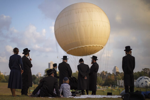 Ultra-Orthodox Jews, some wearing protective face masks amid concerns over the country's coronavirus outbreak, spend the day at a park in Tel Aviv, Israel, Wednesday, Aug. 12, 2020. Ultra-Orthodox Yeshivas students enjoy Bein Hazmanim (