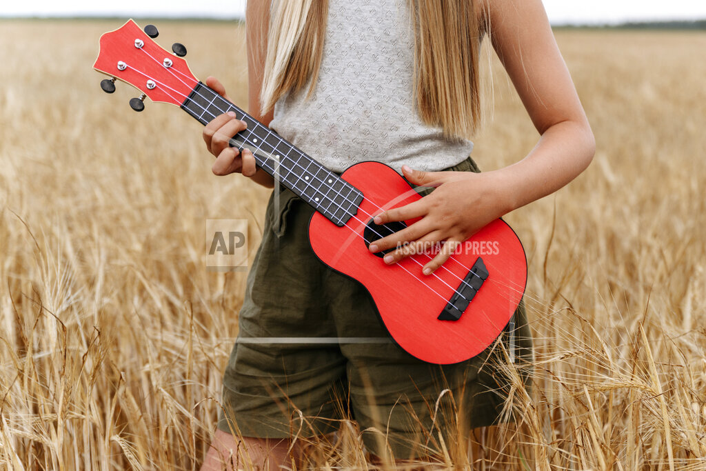 Girl playing guitar while standing on wheat field