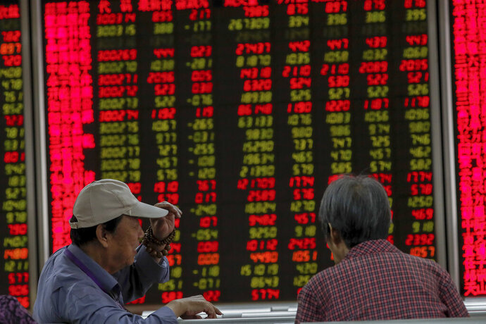 Chinese investors monitor stock prices at a brokerage house in Beijing, Thursday, Sept. 19, 2019. Shares were mixed in Asia on Thursday, with Tokyo and Sydney logging modest gains after the Federal Reserve cut its benchmark interest rate for a second time this year, citing slowing global economic growth and uncertainty over U.S. trade conflicts. (AP Photo/Andy Wong)