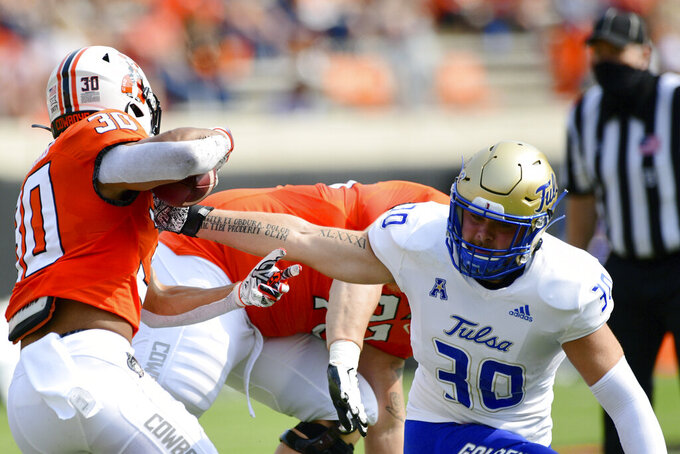 Tulsa linebacker Justin Wright (30) reaches for the ball controlled by Oklahoma State running back Chuba Hubbard (30) in the first half of an NCAA college football game, Saturday, Sept. 19, 2020, in Stillwater, Okla. (AP Photo/Brody Schmidt)