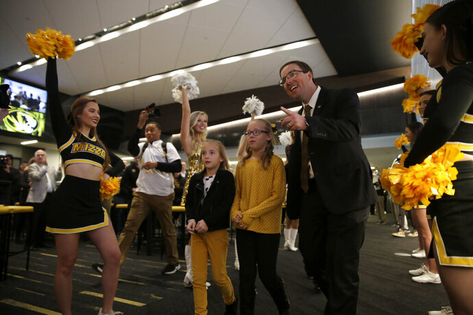 ADDS THE CHILDREN'S NAMES - Eliah Drinkwitz walks to the stage to be introduced as the new NCAA college football head coach at the University of Missouri, with his children Emerson, 6, left, and Addison, 9, Tuesday, Dec. 10, 2019, in Columbia, Mo. Drinkwitz becomes the 33rd head football coach at Missouri after coaching the 2019 season at Appalachian State. (AP Photo/Jeff Roberson)