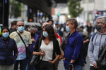 People wearing face masks to prevent the spread of coronavirus queue to buy lottery tickets  in downtown Madrid, Spain, Friday, Sept. 18, 2020. With more than 11,000 new daily coronavirus cases, the attention in Spain is focusing on its capital, where officials are mulling localized lockdowns and other measures to bring down the curve of contagion. (AP Photo/Manu Fernandez)