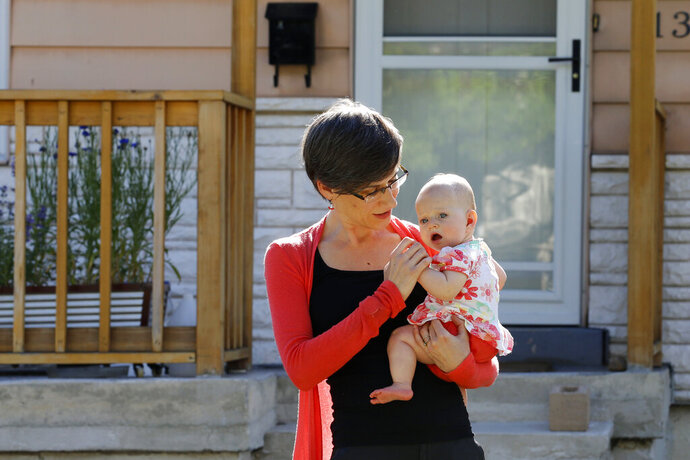 In this Friday, May 29, 2020, photo, Sara Adelman holds her daughter Amelia in Salt Lake City. Adelman is burning through her vacation time to help manage her current status as a working-from-home mom since her daughter's daycare closed due to the coronavirus pandemic. (AP Photo/Rick Bowmer)