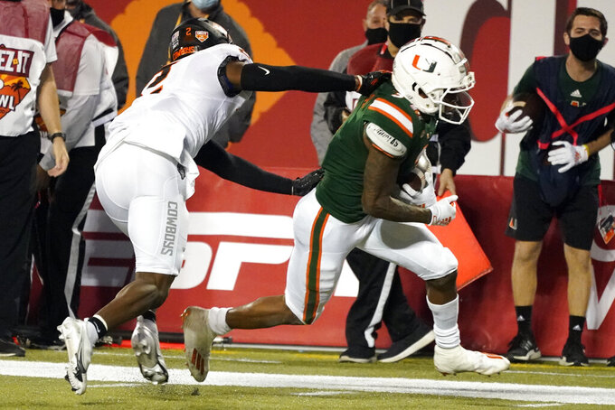 Miami wide receiver Mike Harley slips past Oklahoma State safety Tre Sterling for a touchdown during the second half of the Cheez-it Bowl NCAA college football game, Tuesday, Dec. 29, 2020, in Orlando, Fla. (AP Photo/John Raoux)