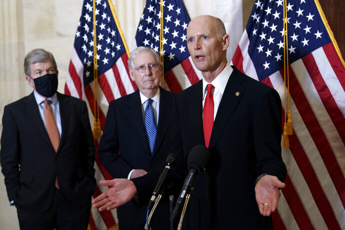 FILE - In this Nov. 10, 2020, file photo Sen. Rick Scott, R-Fla., joined at center by Senate Majority Leader Mitch McConnell, R-Ky., and Sen. Roy Blunt, R-Mo., far left, speaks to reporters briefly following a closed-door meeting where the Republican Conference held leadership elections, on Capitol Hill in Washington. (AP Photo/J. Scott Applewhite, File)