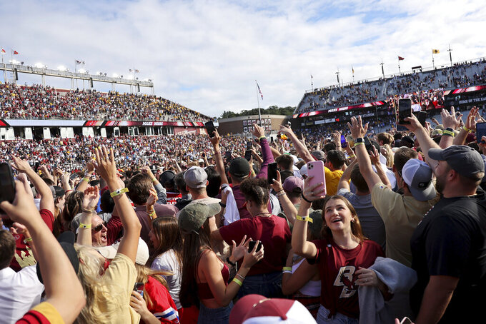 Boston College fans celebrate on the field after the football team defeated Missouri in an NCAA college football game, Saturday, Sept. 25, 2021, in Boston. (AP Photo/Mary Schwalm)