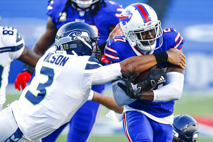 Buffalo Bills' Tre'Davious White (27) runs back an interception as Seattle Seahawks quarterback Russell Wilson (3) attempts to tackle him during the second half of an NFL football game Sunday, Nov. 8, 2020, in Orchard Park, N.Y. (AP Photo/John Munson)