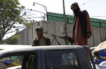 Taliban fighters stand guard on the back of vehicle with a machine gun in front of main gate leading to Afghan presidential palace, in Kabul, Afghanistan, Monday, Aug. 16, 2021. The U.S. military has taken over Afghanistan's airspace as it struggles to manage a chaotic evacuation after the Taliban rolled into the capital. (AP Photo/Rahmat Gul)