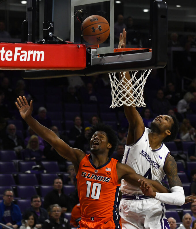 Illinois guard Andres Feliz (10) misses a shot as Northwestern forward Vic Law (4) deflects it during the second half of an NCAA college basketball game on Sunday, Jan. 6, 2019, in Evanston, Ill. (AP Photo/Matt Marton)