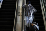 A woman wearing a disposable rain poncho rides an escalator to board her plane at the Los Angeles International Airport in Los Angeles, Monday, Nov. 23, 2020. About 1 million Americans a day packed airports and planes over the weekend even as coronavirus deaths surged across the U.S. and public health experts begged people to stay home and avoid big Thanksgiving gatherings. (AP Photo/Jae C. Hong)