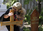 A woman with dog kisses the wooden cross atop the former strongman Slobodan Milosevic grave during funeral of his wife Mirjana Markovic, marker on right, at the yard of his estate in his home town of Pozarevac, Serbia, Saturday, April 20, 2019. Markovic died last week in Russia where she had been granted asylum. The ex-Serbian first lady had fled there in 2003 after Milosevic was ousted from power in a popular revolt and handed over to the tribunal in The Hague, Netherlands. (AP Photo/Darko Vojinovic)