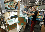 FILE - In this March 12, 2019, file photo, Yakaranday Arce packs sold clothing for shipment at the ThredUp sorting facility in Phoenix.  J.C. Penney and Macy's are in the midst of rolling out a few dozen ThredUp branded shops each in time for the back-to-school shopping season.The partnerships follow a similar deal with department store retailer Stage Stores. (AP Photo/Matt York, File)