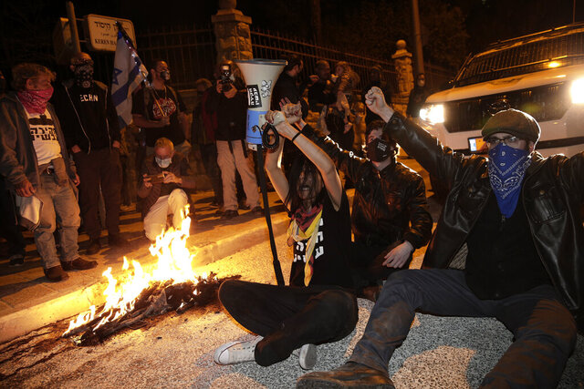 Israeli protesters chant slogans and block a road during a demonstration against Israeli Prime Minister Benjamin Netanyahu near his official residence in Jerusalem during the third nationwide coronavirus lockdown, Saturday, Jan. 2, 2021. (AP Photo/Ariel Schalit)