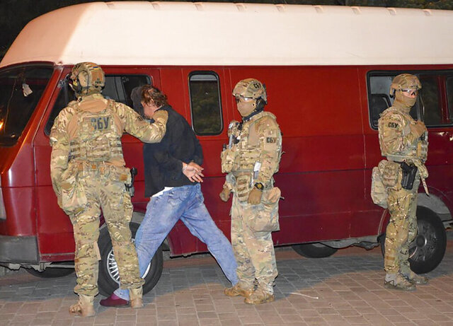 An assailant, who has seized a long-distance bus with 13 hostages, after police officers captured him in the city centre of Lutsk, some 400 kilometers (250 miles) west of Kyiv, Ukraine, on Tuesday late, July 21, 2020. Ukrainian police say the armed man who seized hostages on a long-distance bus in the western city of Lutsk has been detained and all the people he held have been freed unharmed after a standoff that lasted more than 12 hours. (Ukrainian Police Press Office via AP)