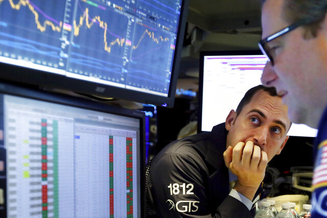 FILE - In this Nov. 14, 2019, file photo a pair of specialists work on the floor of the New York Stock Exchange. Corporate profits continued their yearlong slide during the third quarter and analysts expect another poor performance before things start improving. (AP Photo/Richard Drew, File)