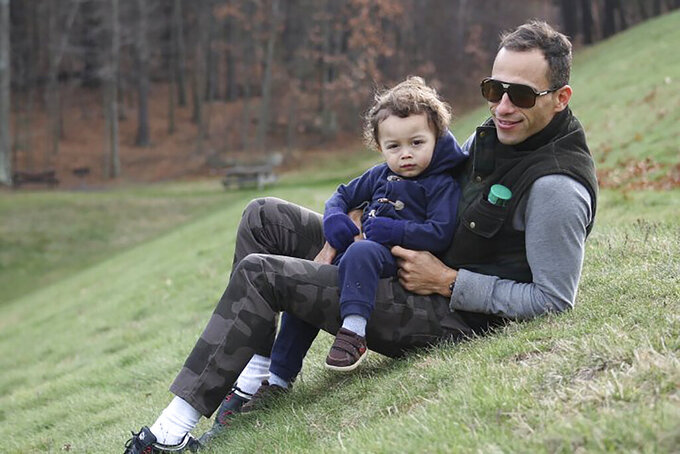 In this Sept. 2014 photo provided by Allison Andrade-Cullen, her husband Flavio Andrade Prado, a Brazilian national, right, holds their son Gabriel Andrade-Cullen, left, while visiting Hopkinton State Park, in Hopkinton, Mass. Andrade Prado is being held by Immigration and Customs Enforcement, or ICE, at the Plymouth County House of Corrections. The number of detainees nationwide has more than doubled since the end of February, to nearly 27,000, according to recent data from U.S. Immigration and Customs Enforcement. (Allison Andrade-Cullen via AP)
