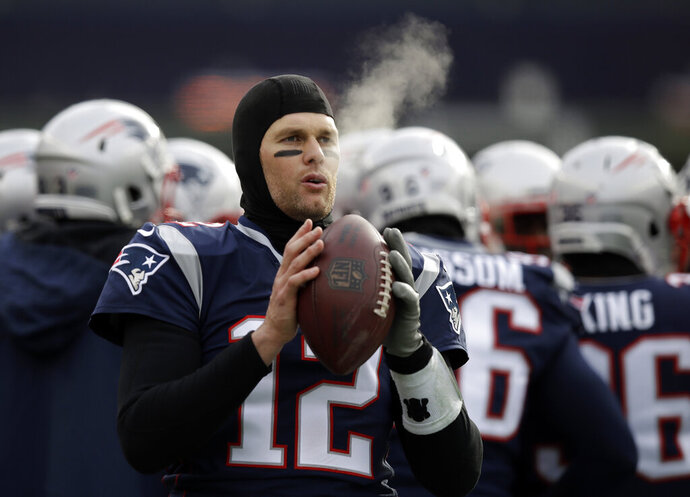 FILE - In this Dec. 31, 2017, file photo, New England Patriots quarterback Tom Brady keeps limber on the sideline in the cold weather during the first half of an NFL football game against the New York Jets, in Foxborough, Mass. His coach downplays it, but Tom Brady knows the cold-weather New England Patriots should have an advantage when they host the warm-weather Los Angeles Chargers in Sunday's AFC Divisional Round game. (AP Photo/Charles Krupa, File)