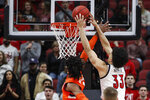Louisville forward Jordan Nwora (33) goes for a dunk as he's fouled by Syracuse forward Quincy Guerrier (1) during the first half of an NCAA college basketball game Wednesday, Feb. 19, 2020, in Louisville, Ky. (AP Photo/Wade Payne)