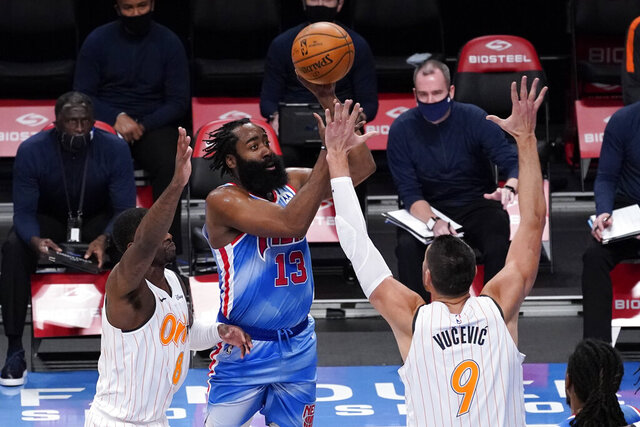 Brooklyn Nets guard James Harden, center, shoots past Orlando Magic forward Dwayne Bacon, left, and center Nikola Vucevic, right, during the first half of an NBA basketball game, Saturday, Jan. 16, 2021, in New York. (AP Photo/Mary Altaffer)