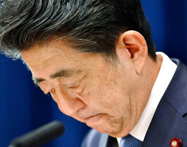 "Japanese Prime Minister Shinzo Abe downs his head as he says he is stepping down during a press conference at the prime minister official residence in Tokyo Friday, Aug. 28, 2020. Japan's longest-serving prime minister Abe said Friday he intends to step down because a chronic health problem has resurfaced. He told reporters that it was ""gut wrenching"" to leave so many of his goals unfinished. (Kyodo News via AP)"