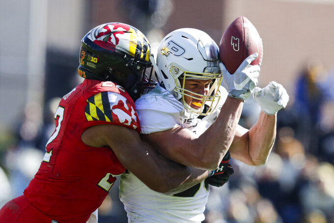 Purdue tight end Brycen Hopkins (89) makes a catch against his helmet as he's hit by Maryland linebacker Isaiah Davis (22) during the second half of an NCAA college football game in West Lafayette, Ind., Saturday, Oct. 12, 2019. Purdue defeated Maryland 40-14. (AP Photo/Michael Conroy)