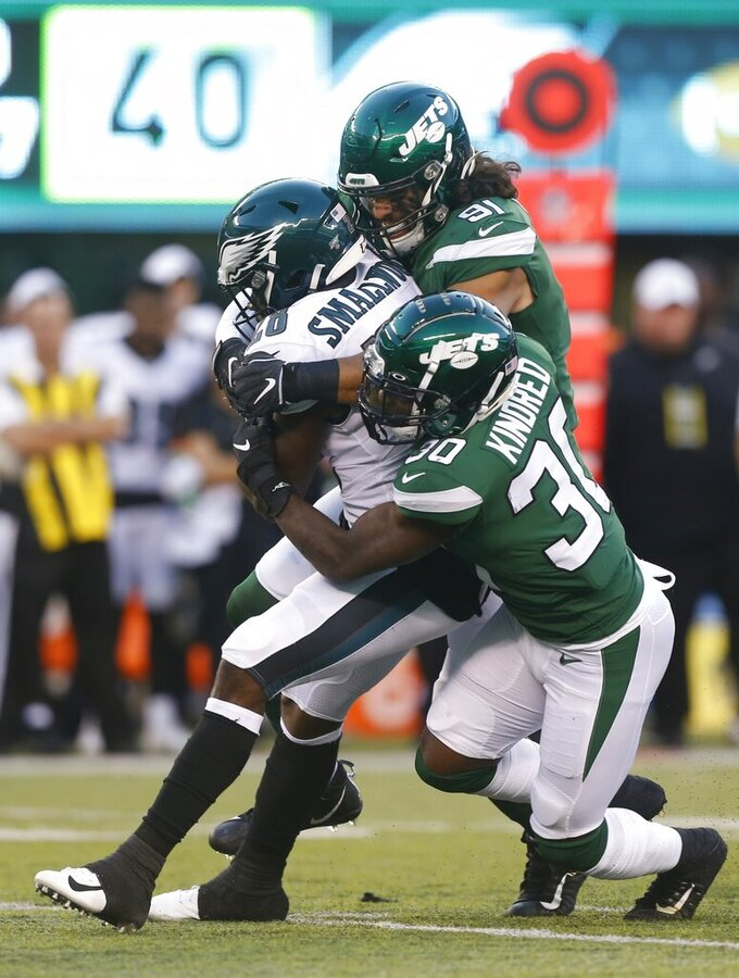 Philadelphia Eagles' Wendell Smallwood (28) is tackled by New York Jets' Derrick Kindred (30) and Bronson Kaufusi (91) during the first half of a preseason NFL football game Thursday, Aug. 29, 2019, in East Rutherford, N.J. (AP Photo/Jim McIsaac)