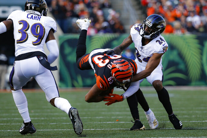 Baltimore Ravens cornerback Brandon Carr (24) tackles Cincinnati Bengals wide receiver Tyler Boyd (83) during the first half of NFL football game, Sunday, Nov. 10, 2019, in Cincinnati. (AP Photo/Frank Victores)