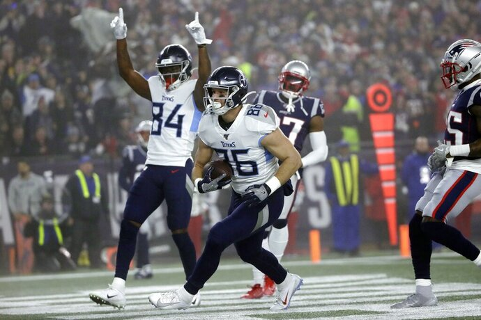Tennessee Titans tight end Anthony Firkser, center, catches a touchdown pass against the New England Patriots in the first half of an NFL wild-card playoff football game, Saturday, Jan. 4, 2020, in Foxborough, Mass. (AP Photo/Elise Amendola)