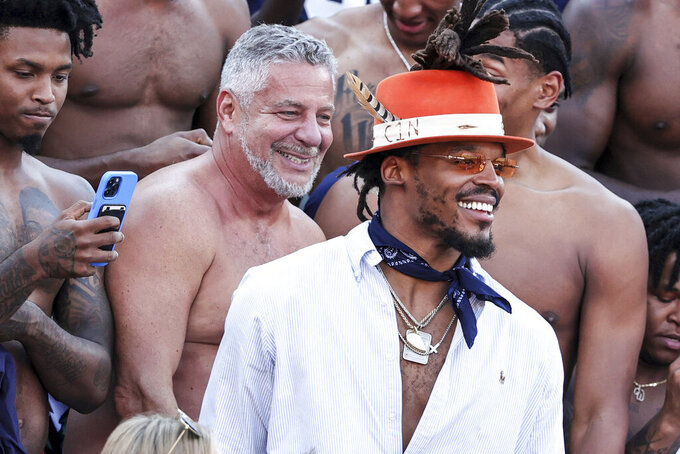 Auburn men's basketball coach Bruce Pearl, left, and former Auburn and NFL quarterback Cam Newton cheer with the fans prior to the start of an NCAA college football game against Georgia Saturday, Oct. 9, 2021 in Auburn, Ala. (AP Photo/Butch Dill)