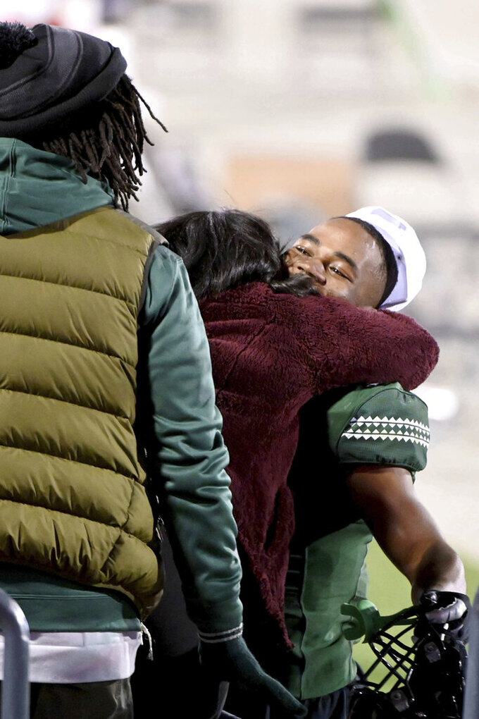 Hawaii running back Dae Dae Hunter (0) celebrates with his family in the stands after his teams 28-14 win over Houston in the New Mexico Bowl NCAA college football game in Frisco, Texas, Thursday, Dec. 24, 2020. (AP Photo/Matt Strasen)