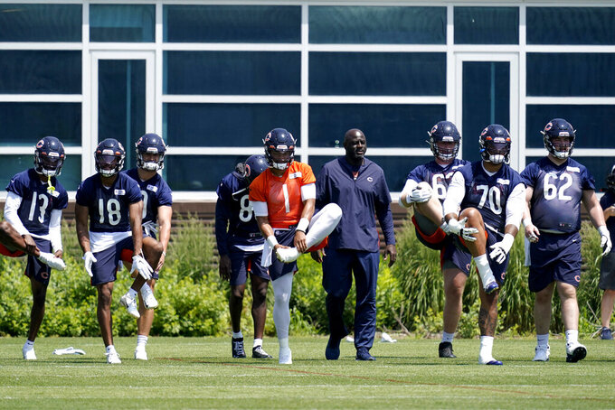 Chicago Bears quarterback Justin Fields (1) stretches on the field with teammates during NFL football practice in Lake Forest, Ill., Wednesday, June 9, 2021. (AP Photo/Nam Y. Huh)