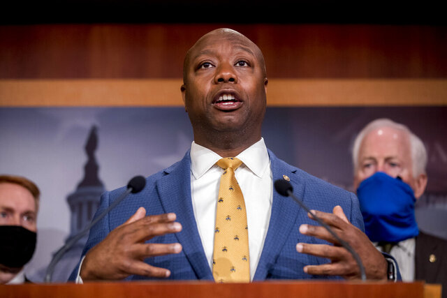 FILE - In this June 17, 2020, file photo, Sen. Tim Scott, R-S.C., accompanied by Republican senators speaks at a news conference to announce a Republican police reform bill on Capitol Hill in Washington. Initially reluctant to speak on race, Scott is now among the Republican Party's most prominent voices teaching his colleagues what it's like to be a Black man in America. (AP Photo/Andrew Harnik, File)
