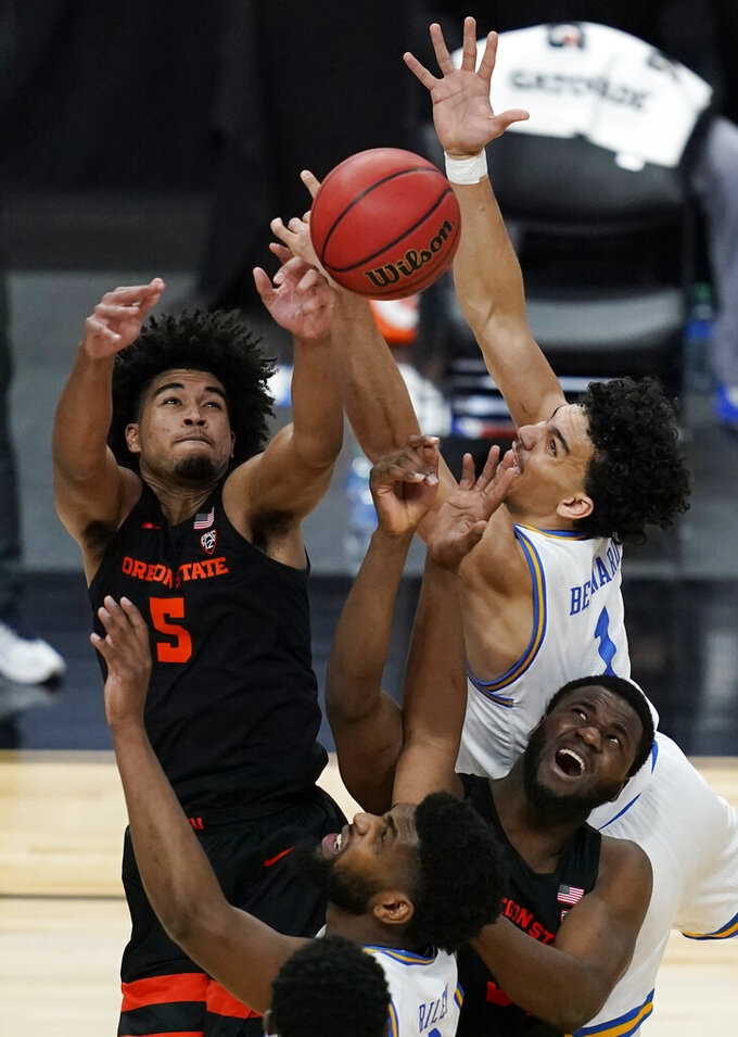 Oregon State's Ethan Thompson, clockwise from top left, UCLA's Jules Bernard, Oregon State's Rodrigue Andela, and UCLA's Cody Riley (2) vie for a rebound during the second half of an NCAA college basketball game in the quarterfinal round of the Pac-12 men's tournament Thursday, March 11, 2021, in Las Vegas. (AP Photo/John Locher)