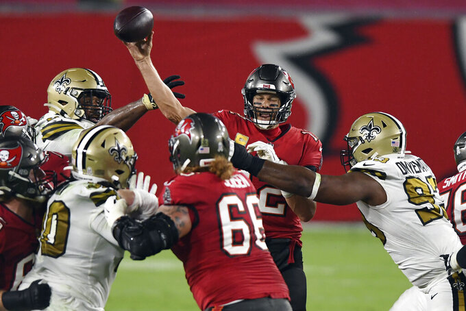 Tampa Bay Buccaneers quarterback Tom Brady (12) winces as he is hit by New Orleans Saints defensive tackle David Onyemata (93) during the first half of an NFL football game Sunday, Nov. 8, 2020, in Tampa, Fla. (AP Photo/Jason Behnken)