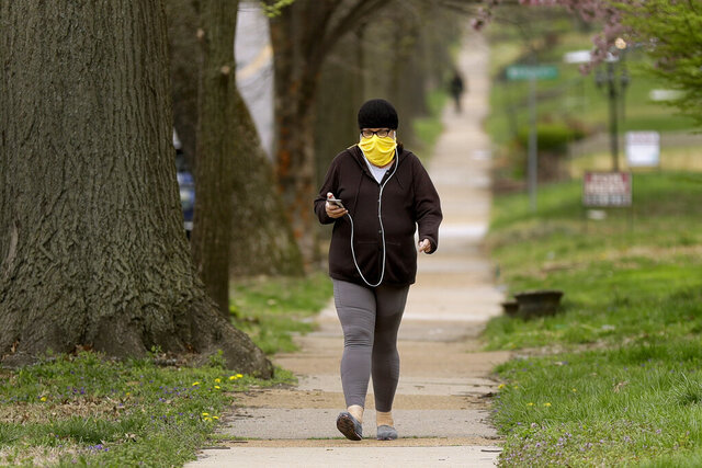 A person covers their face with a scarf while walking down the street Monday, April 6, 2020, in University City, Mo. The Centers for Disease Control and Prevention now recommends wearing cloth face coverings in public settings after recent studies have shown a significant portion of the population can transmit the coronavirus without showing any symptoms. (AP Photo/Jeff Roberson)