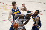 Utah Jazz guard Jordan Clarkson, front left, is trapped in the corner with the ball by Denver Nuggets guard Monte Morris, front right, and center Isaiah Hartenstein in the first half of an NBA basketball game Sunday, Jan. 17, 2021, in Denver. (AP Photo/David Zalubowski)