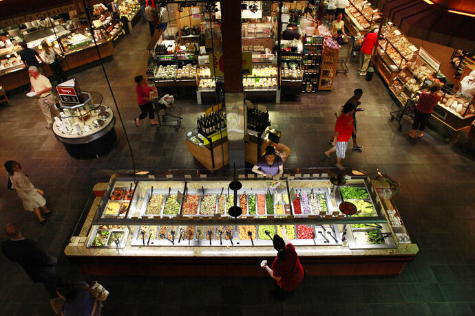 FILE - In this May 27, 2010, file photo customers shop at the salad bar for lunch at the Market Cafe in the Wegmans grocery store in Fairfax, Va. New Yorkers are flocking to greet a new arrival to the city, Wegmans grocery store. The popular regional chain officially opened its first New York City outpost Sunday, Oct. 27, 2019, a 74,000-square-foot (6,875-sq. meter) store at the Brooklyn Navy Yard with more than 500 employees. (AP Photo/Jacquelyn Martin, File)