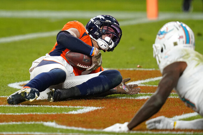 Denver Broncos free safety Justin Simmons falls after intercepting a pass in the end zone against the Miami Dolphins during the second half of an NFL football game, Sunday, Nov. 22, 2020, in Denver. (AP Photo/David Zalubowski)