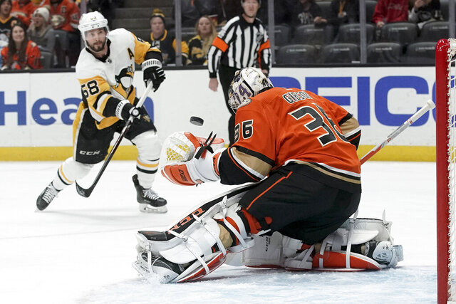 Anaheim Ducks goaltender John Gibson blocks a shot by Pittsburgh Penguins defenseman Kris Letang during the first period of an NHL hockey game in Anaheim, Calif., Friday, Feb. 28, 2020. (AP Photo/Chris Carlson)