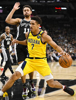 Indiana Pacers' Malcolm Brogdon (7) drives against San Antonio Spurs' Bryn Forbes during the first half of an NBA basketball game, Monday, March 2, 2020, in San Antonio. (AP Photo/Darren Abate)