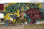 Veronica Carbajal places a candle at a mural for Army Spc. Vanessa Guillen in Austin, Texas, on Monday July 6, 2020. Guillen went missing from Fort Hood in April, and is believed to have been killed by another soldier. The mural was created Saturday and Sunday by artists Fili Mendieta and Arturo Silva. (Jay Janner/Austin American-Statesman via AP)