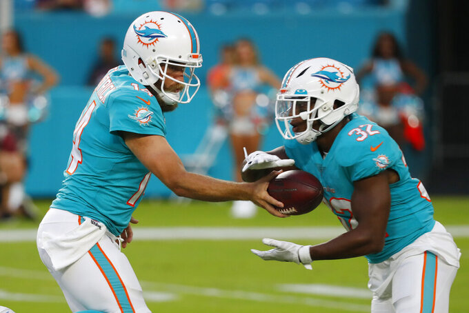 Miami Dolphins quarterback Ryan Fitzpatrick (14) hands off the football to running back Kenyan Drake (32) during the first half of a preseason NFL football game against the Atlanta Falcons, Thursday, Aug. 8, 2019, in Miami Gardens, Fla. (AP Photo/Wilfredo Lee)