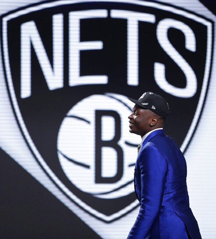 Florida State's Mfiondu Kabengele walks onstage after the Brooklyn Nets selected him as the 27th pick overall in the NBA basketball draft Thursday, June 20, 2019, in New York. (AP Photo/Julio Cortez)