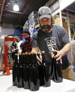 In this March 4, 2019, photo, brewery founder Jamie Adams, right, and John Condzella bottle a batch of their Dubbel beer at the St. James Brewery in Holbrook, N.Y. Adams recently introduced an ale called Deep Ascent at a New York craft beer festival after he created it, using the yeast from the bottles recovered from the SS Oregon, a Liverpool-to-New York luxury liner that sank off Fire Island in 1886. (AP Photo/Seth Wenig)
