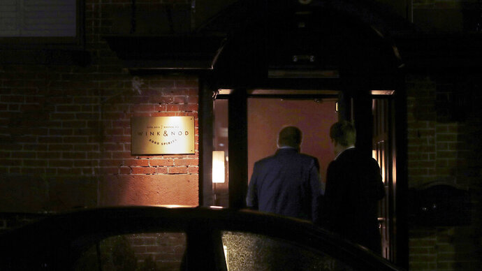 In this Dec. 10, 2019, photo two patrons walk through the barely lit, nondescript doorway leading to the Wink & Nod basement-dwelling, speakeasy-like bar in Boston. Americans are consuming more alcohol per capita now than in the time leading up to Prohibition. (AP Photo/Charles Krupa)
