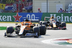 Mclaren driver Daniel Ricciardo of Australia steers his car in front of Red Bull driver Max Verstappen of the Netherlands during the Italian Formula One Grand Prix, at Monza racetrack, in Monza, Italy, Sunday, Sept.12, 2021. (AP Photo/Luca Bruno)