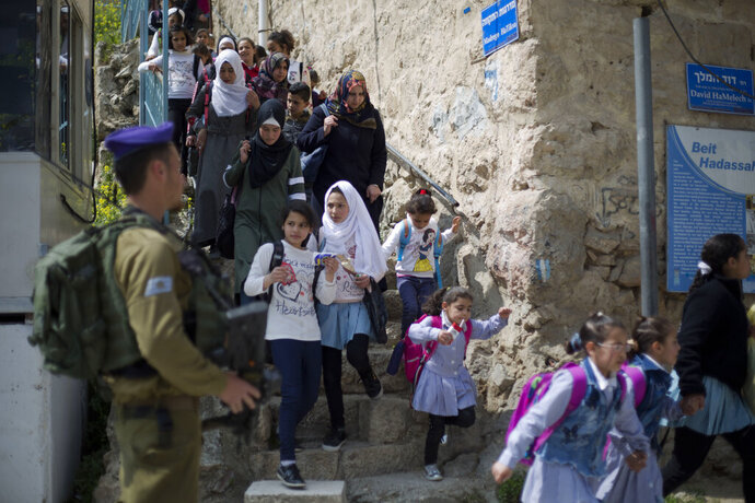 FILE - In this March 21, 2019 file photo, an Israeli solider stands guard as Palestinian school children cross back from school in the Israeli controlled part of the West Bank city of Hebron.  Israeli Prime Minister Benjamin Netanyahu vowed Monday Sept. 16, 2019, to annex